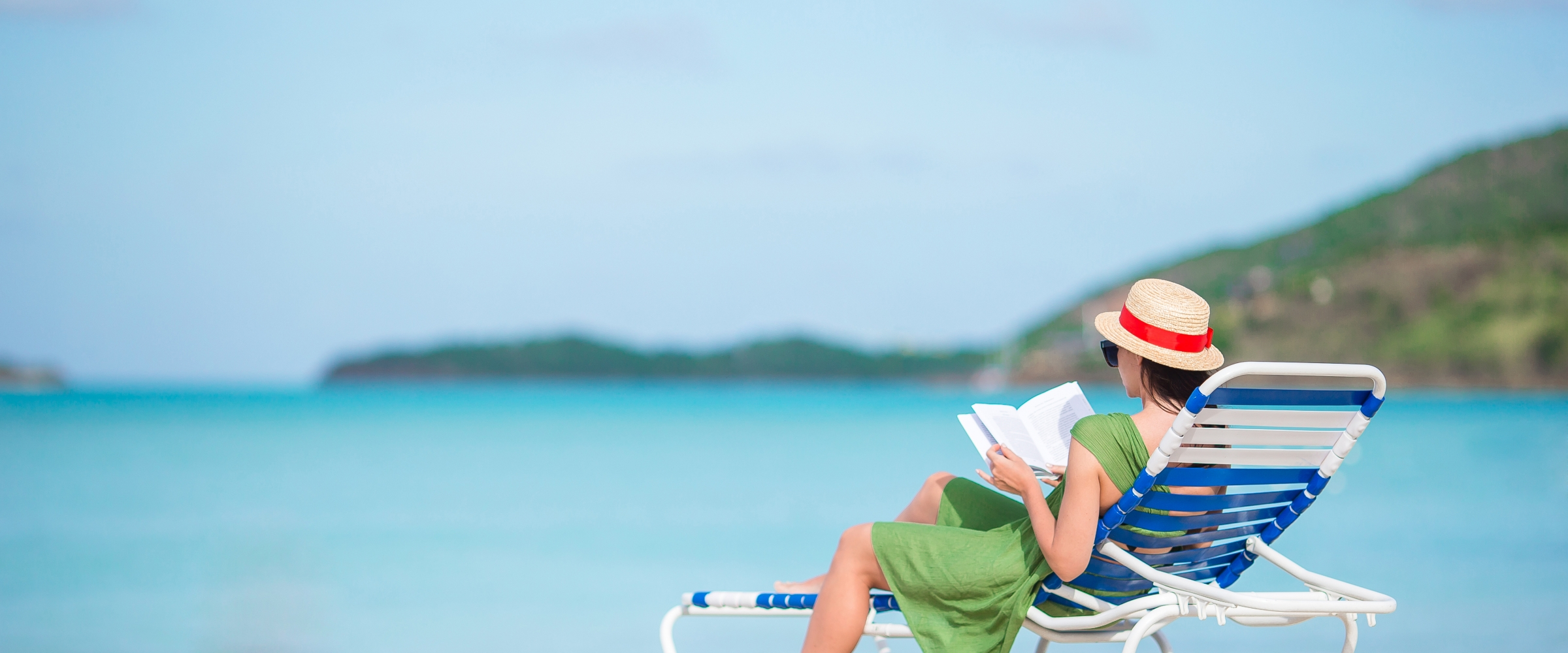 Young woman reading a Georgia Kains book on chaise-lounge on the beach